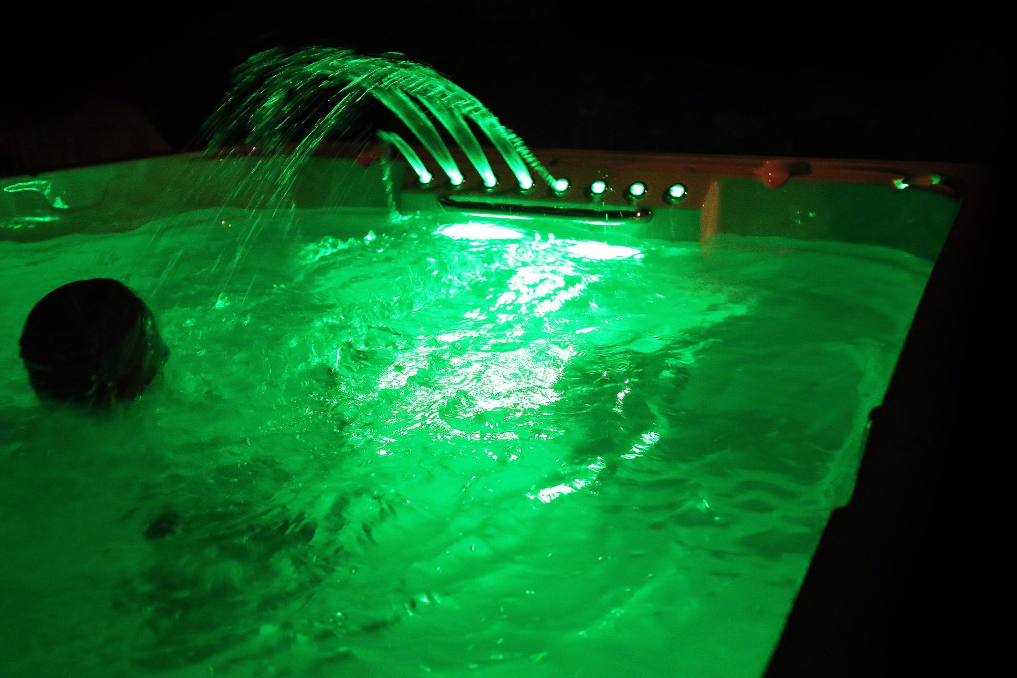 Swimmer in swim spa with Nothern Lights and Waterfall Jets