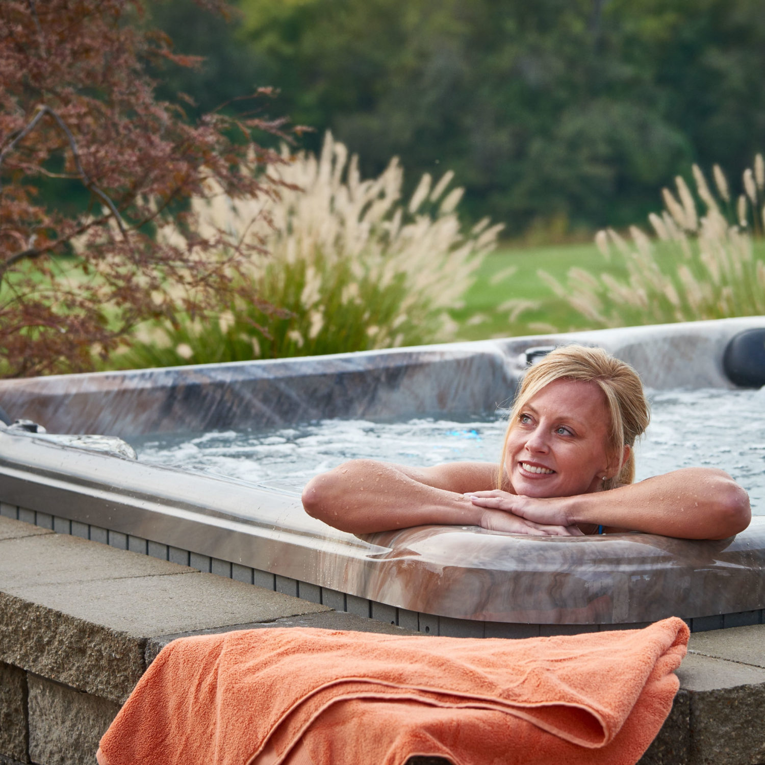 A woman relaxing and smiling in an Aspen Spas Relax hot tub