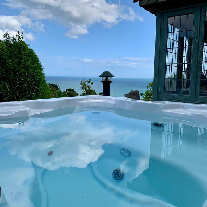 Aspen Tao hot tub next to a summerhouse, underneath a blue summer sky with white clouds, reflecting in the water